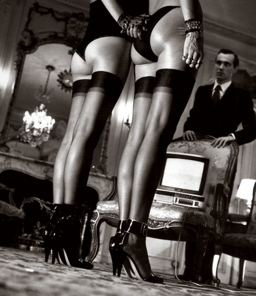Two pairs of legs in black stockings by Helmut Newton